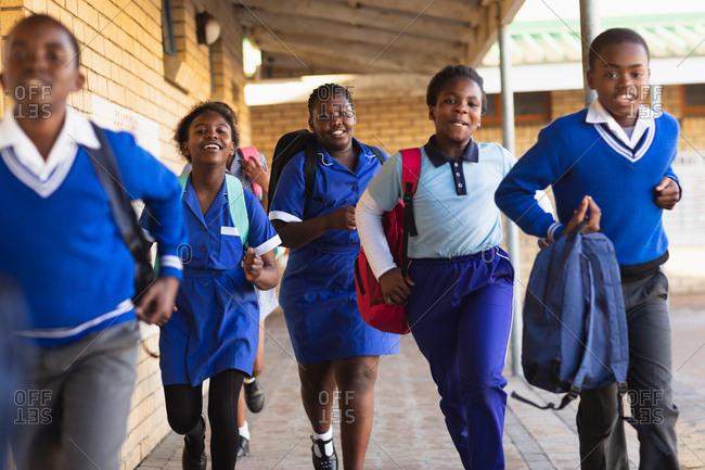 Front view close up of young African schoolboys and schoolgirls running in the school yard carrying schoolbags at a township elementary school