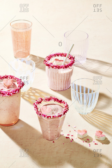 Strawberry milkshakes in a variety of cups