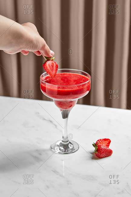 Tasty aromatic smoothie and hand putting sliced strawberry into bowl on marble table