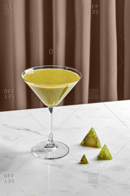 Fresh fragrant kiwi smoothie in glass bowl and kiwi ice triangles on marble table