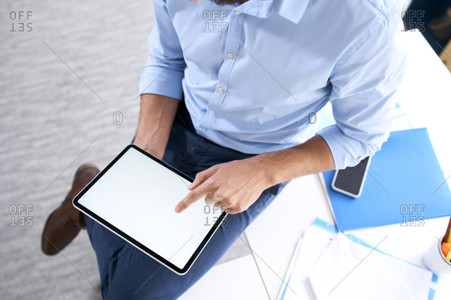Overhead view of a businessman using a digital tablet