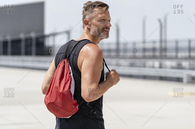 Sporty man carrying a pouch