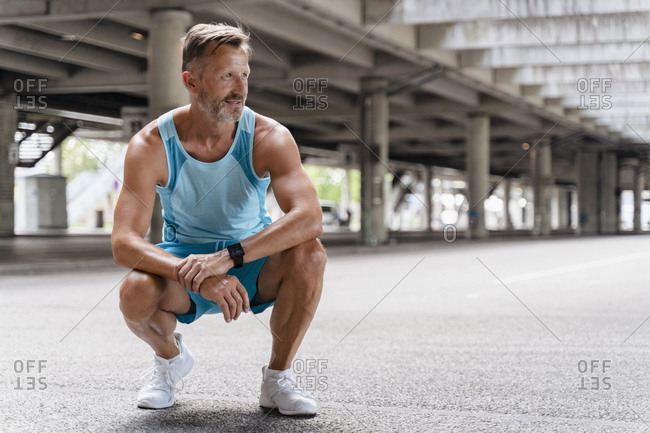 Sporty man crouching outdoors