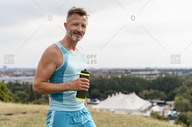 Sporty man with drinking bottle in a park