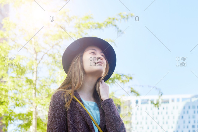 Portrait of woman at backlight wearing hat looking at distance