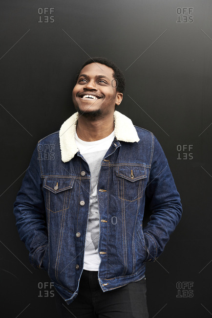 Portrait of laughing man wearing denim jacket standing in front of dark background looking up