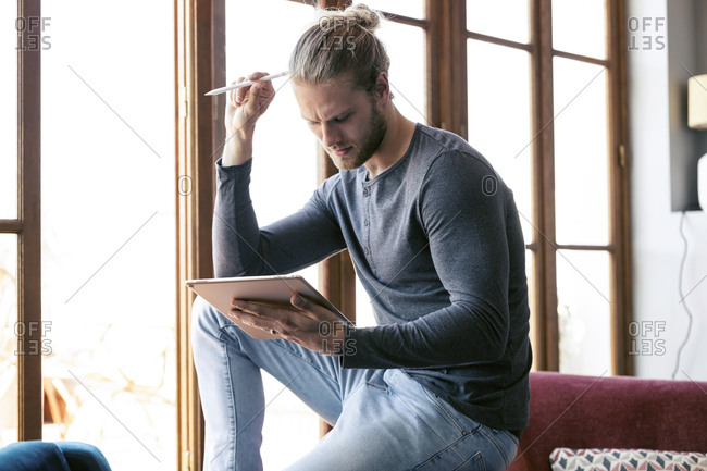 Young man at home using a digital tablet