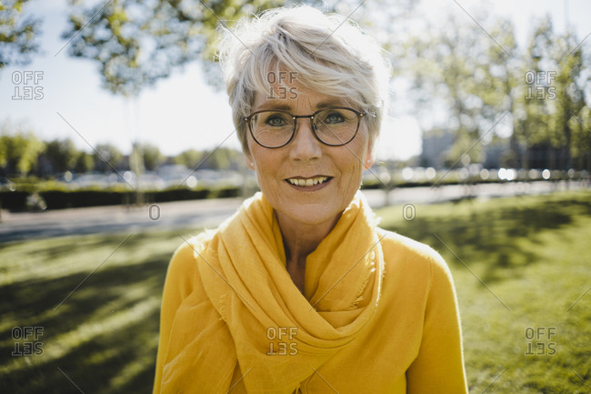Portrait of smiling mature woman with grey hair wearing glasses and yellow clothes