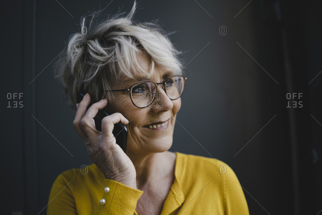 Portrait of mature businesswoman with grey hair on the phone