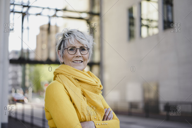 Portrait of mature woman with grey hair wearing glasses and yellow clothes