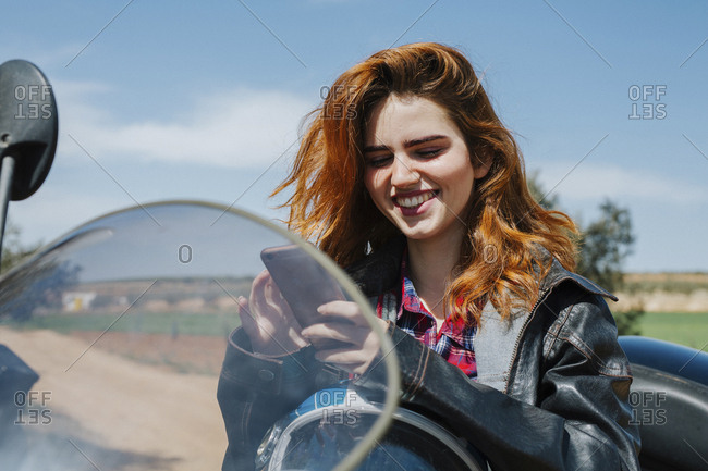 Portrait of happy redheaded woman on motorbike looking at cell phone