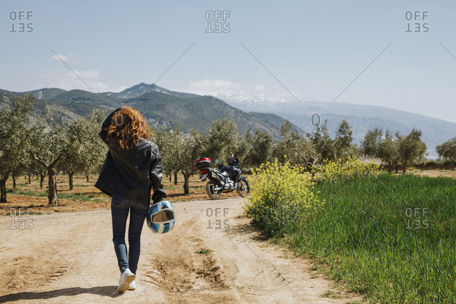 Back view of redheaded motorcyclist walking on dirt track- Andalusia- Spain