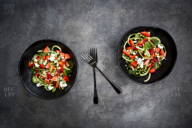 Two bowls of strawberry cucumber salad with feta- mint and balsamic vinegar
