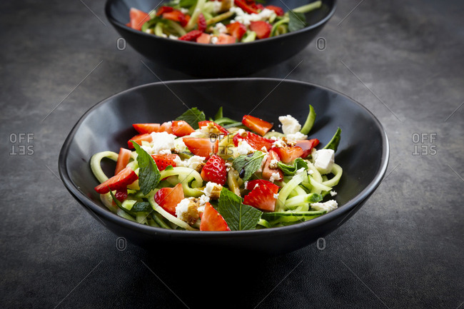 Bowls of strawberry cucumber salad with feta- mint and balsamic vinegar
