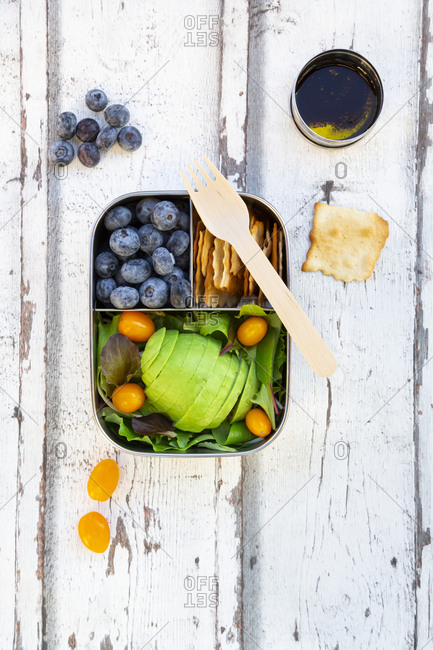 Lunchbox with salad- avocado and yellow tomatoes- crackers- blueberries and salad dressing