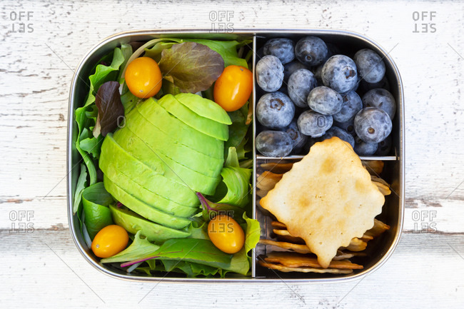 Lunchbox with salad- avocado and yellow tomatoes- crackers and blueberries