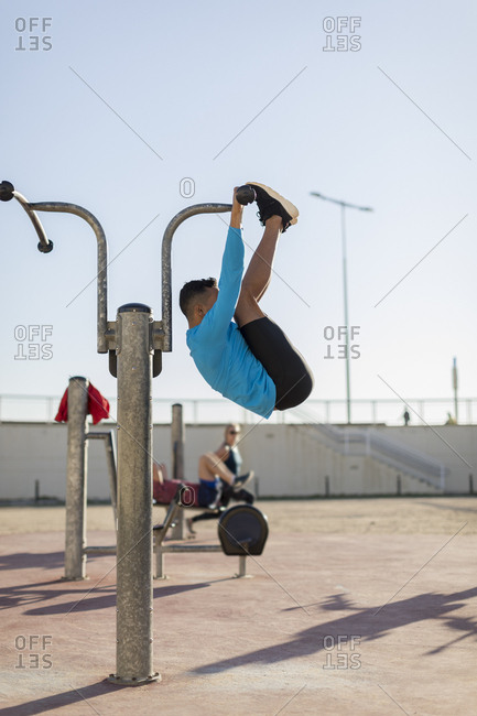 Man doing workout at exercise equipment outdoors