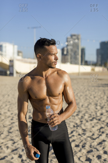 Sporty bare-chested man on the beach
