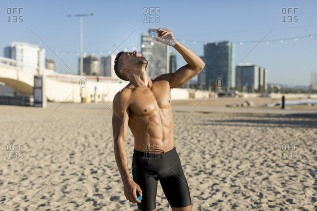 Barechested man drinking water after workout on the beach