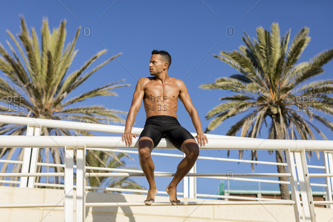 Sporty bare-chested man on the promenade