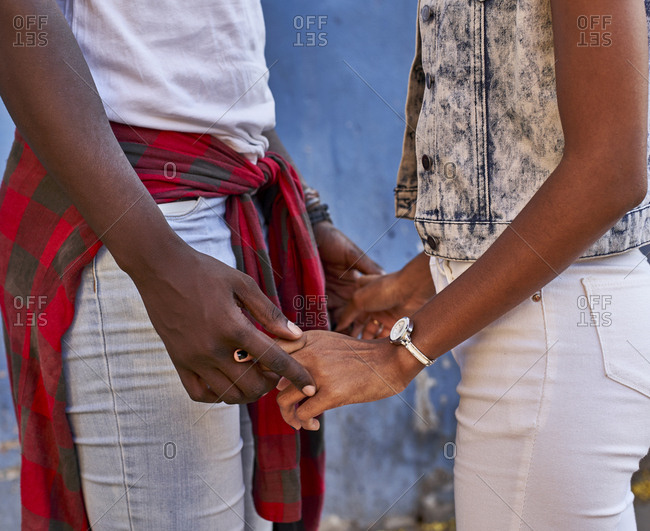 Romantic couple holding hands- close up