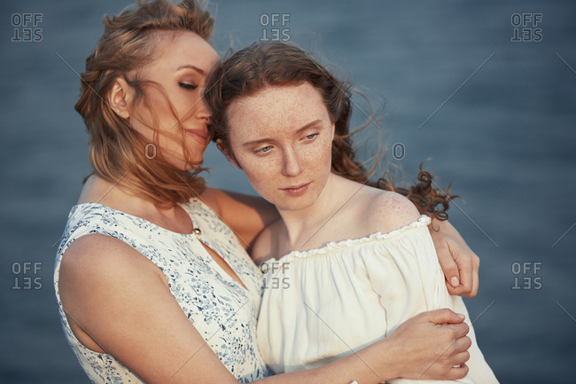 Mother hugging her daughter at the sea