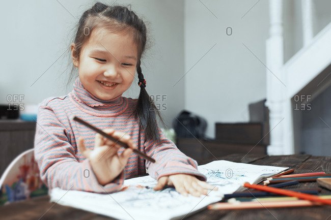 Girl sitting at a table, drawing with colored pencils