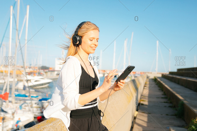 Happy young woman listening to music on her phone