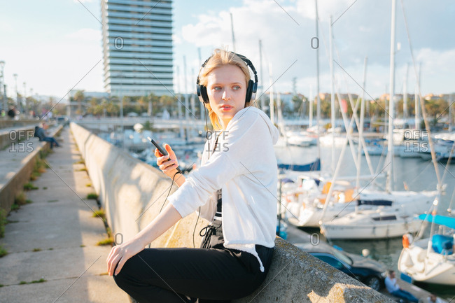 Blonde woman listening to music outside