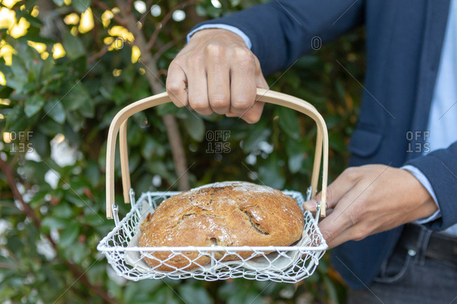 Man holding artisanal loaf of bread in a basket