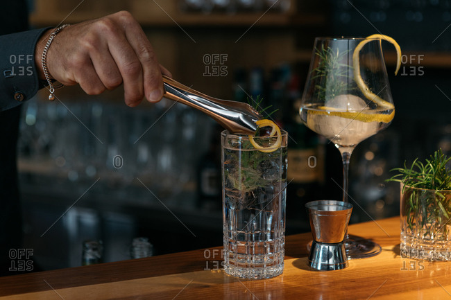 Bartender garnishing a drink with lemon peel
