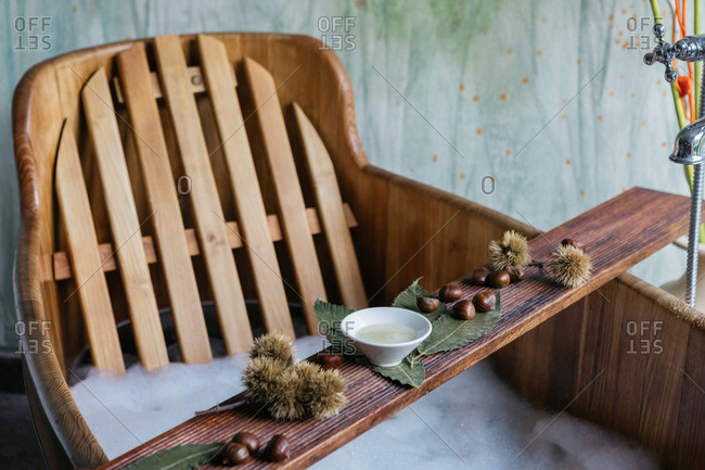 Overhead view of chestnuts and sauce on a wooden board over wooden bathtub