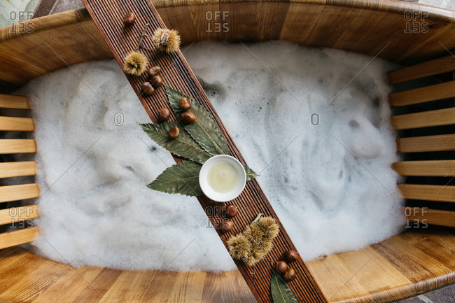Chestnuts and sauce on a wooden board over wooden bathtub