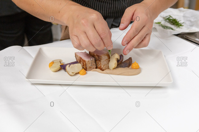 Chef preparing a gourmet meat and mushroom dish in restaurant
