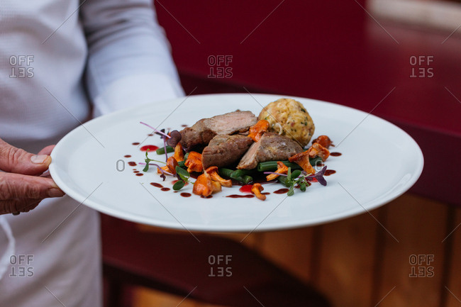 Chef carrying a gourmet meat dish with vegetables