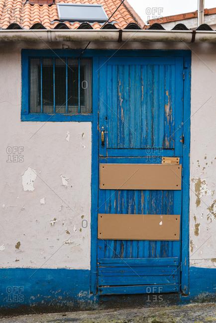 Old blue door of storage room for fishermen in Asturias, Spain