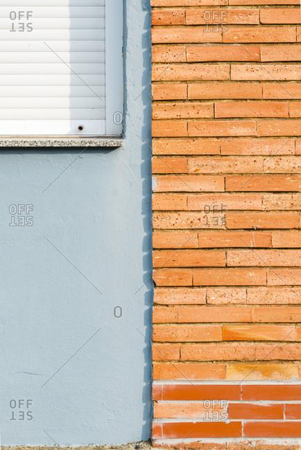 Wall of orange bricks close to window with white blind