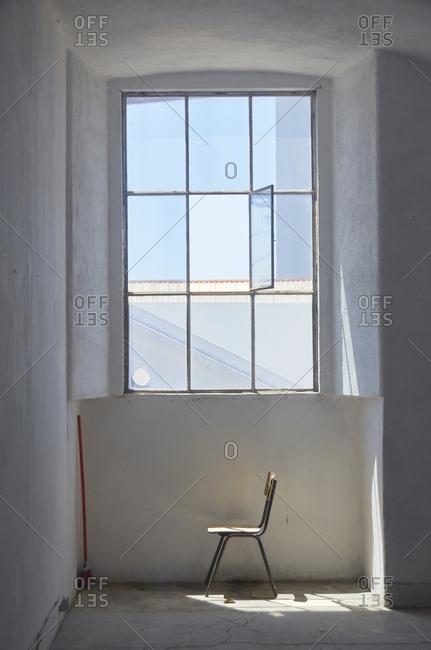 Chair near a window inside home in Lisbon, Portugal