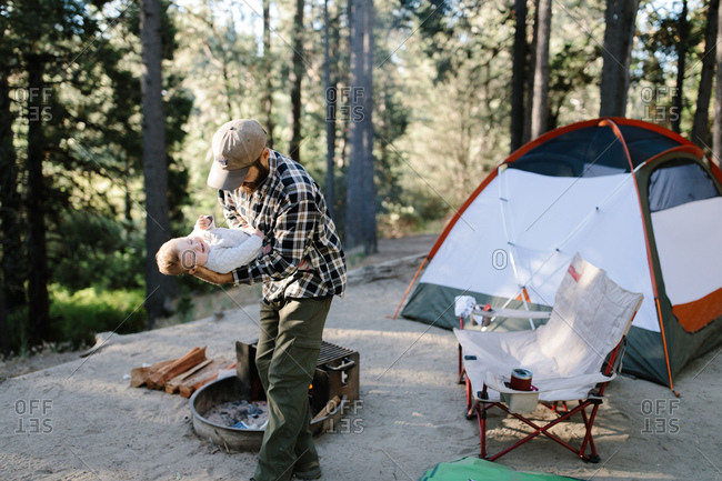 Father and baby daughter camping in the woods and playing together