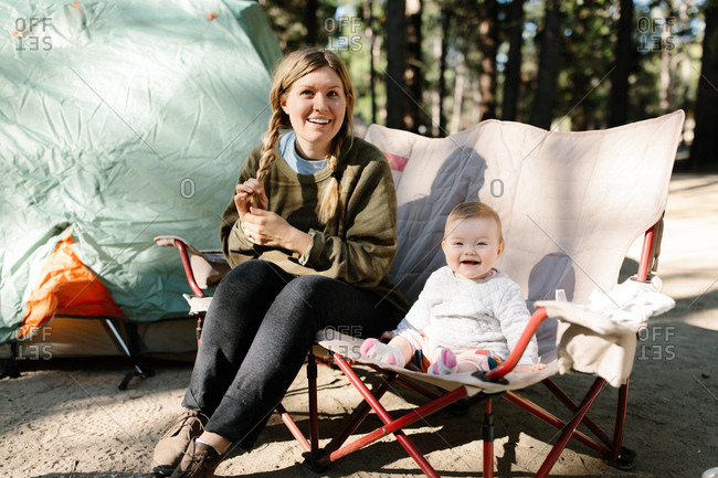 Mother and her baby girl sitting on a camp chair outdoors while camping