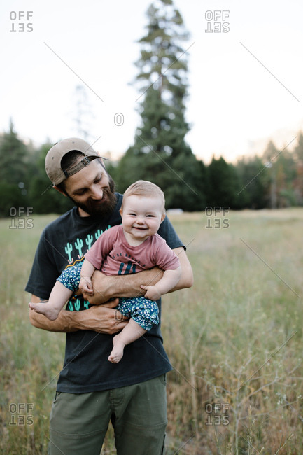 Father and baby daughter smiling in a meadow
