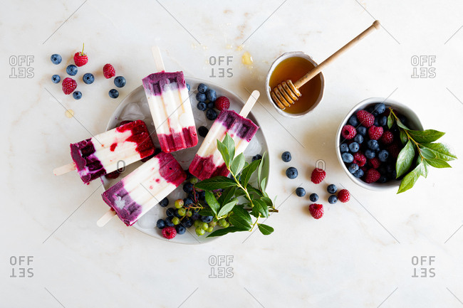 Mixed Berry Popsicles set with fresh berries on ice