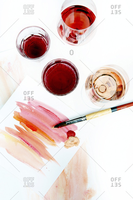 High angle view of watercolor paints with paper and paintbrush by drinks on table