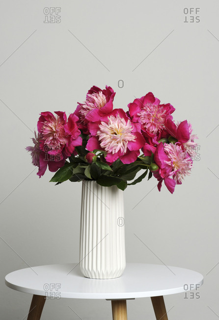 Close-up of pink flowers in vase on stool against gray background