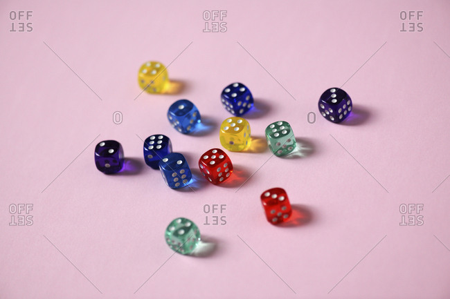 Close-up of colorful dice over pink background