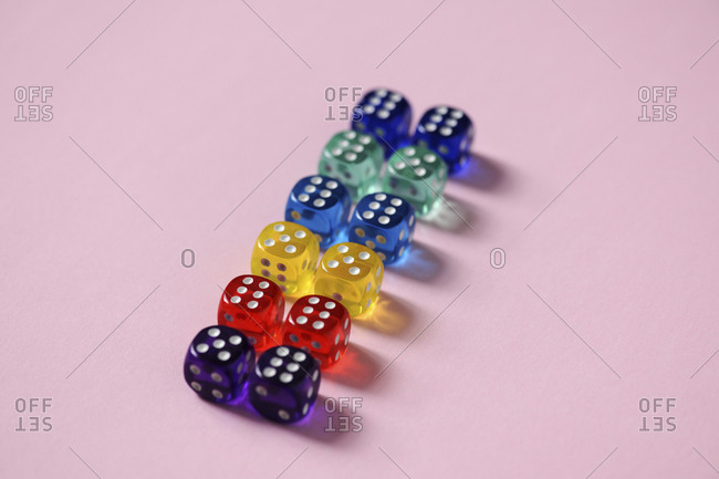 Close-up of colorful dice arranged over pink background