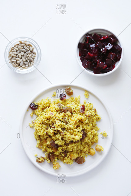 Overhead view of couscous served in plate with beetroot salad and seeds in bowls on white background