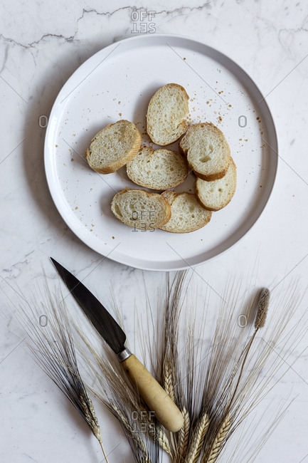 High angle view of bread in plate with wheat and knife on marble table