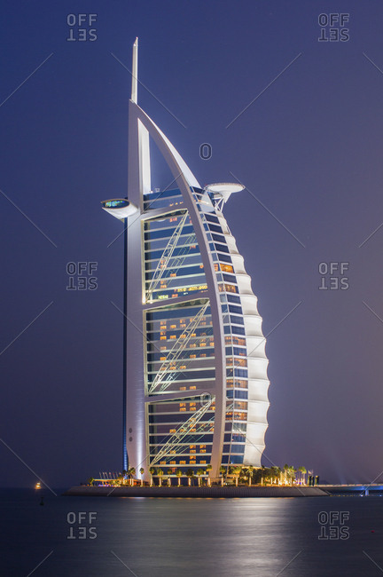 United Arab Emirates, Dubai - January 22, 2010: Illuminated Burj Al Arab Hotel by island against blue sky at night