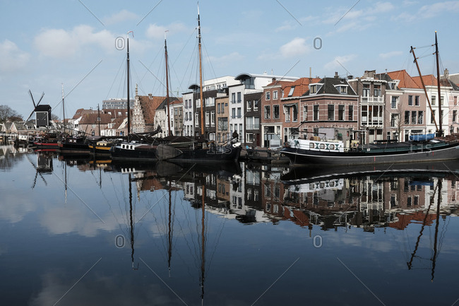 The Netherlands, Leiden - March 26, 2018: Boats moored at harbor against buildings in city
